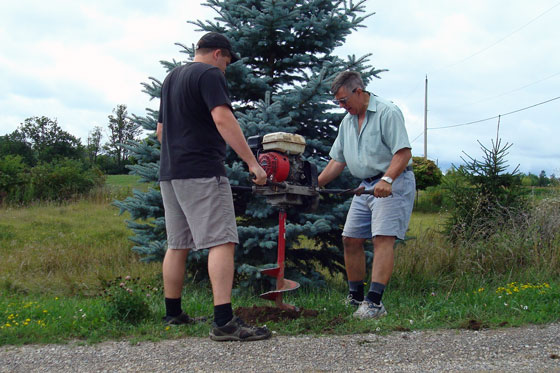 Drilling post holes with an auger