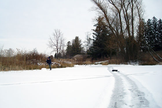 Shovelling the snow off the frozen pond