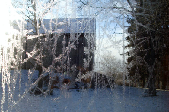 Looking towards the barn through melting frost on the window