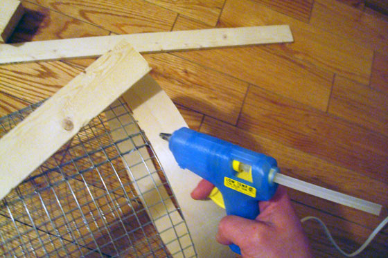 Using a glue gun to stick wood to wire mesh