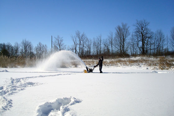 Snow blowing the frozen pond