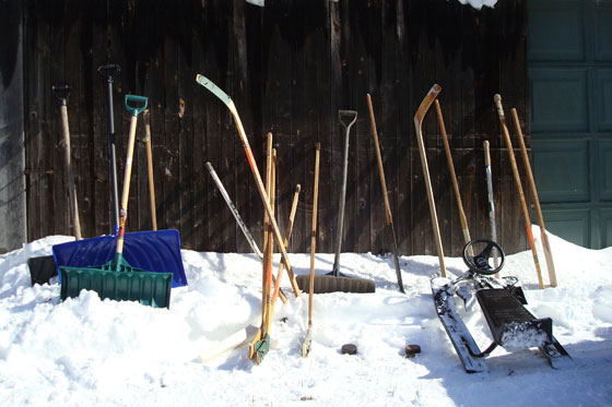 Hockey sticks, snow shovels and a GT snow racer in a snow bank