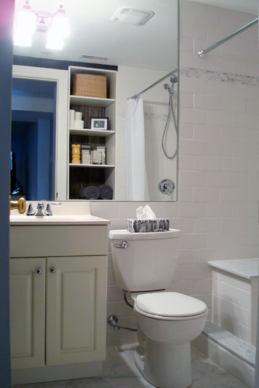 Small basement bathroom with white tile and big mirror