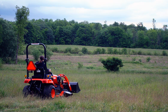 Driving our Kioti CS 2410 tractor across a grassy field