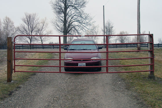 Car behind a closed farm gate