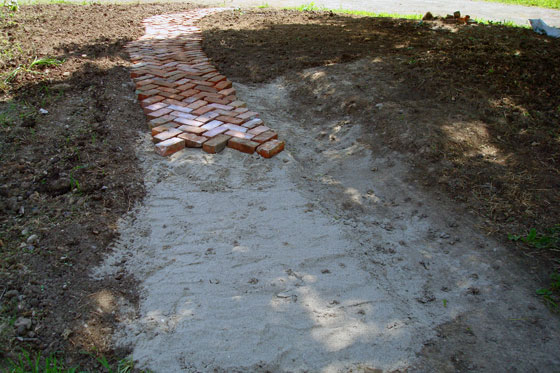 Brick pathway laid in a herring bone pattern on a bed of sand