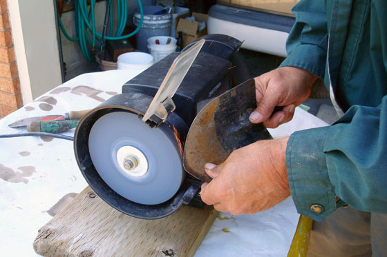Sharpening a small shovel on a grinder
