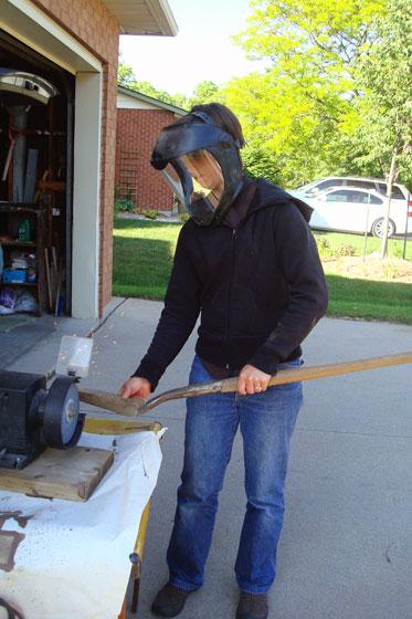 Sharpening a shovel on a grinder