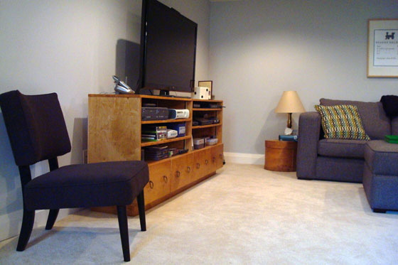 Dark grey occasional chair and grey sectional in a TV room