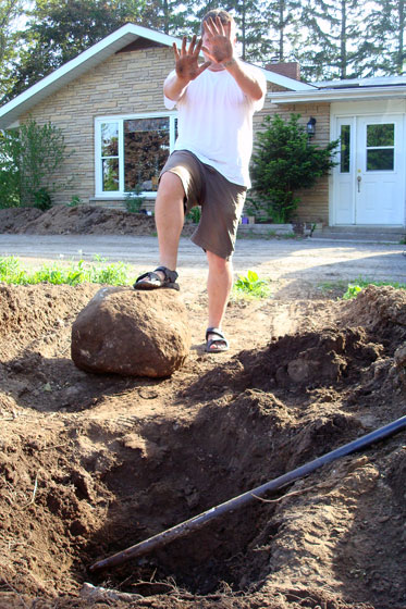 Digging up a large rock from our brick pathway