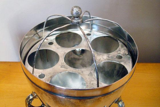 Egg holder inside a silver antique egg coddler