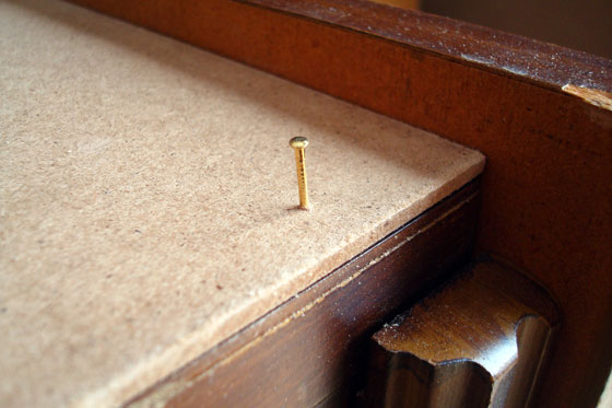 Tacking a board in place with small brass finishing nail