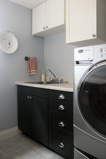 Black and white shaker cabinets with chrome hardware in the laundry room