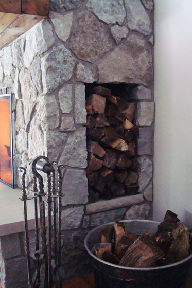 Woodbox in the side of a fieldstone fireplace