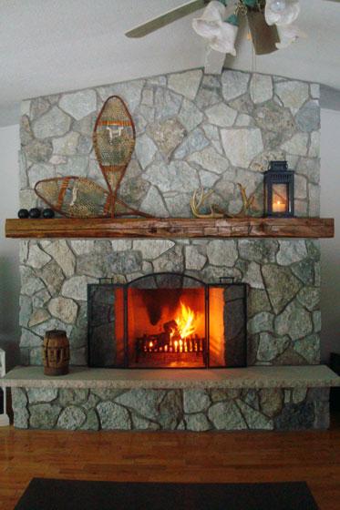 Fieldstone fireplace with barn beam mantel