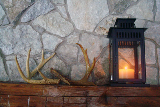 Deer antlers and Ikea Borrby lantern on a barn beam mantel