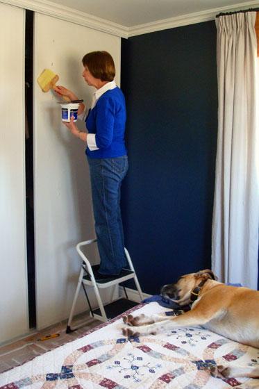Brushing wallpaper paste onto the closet doors