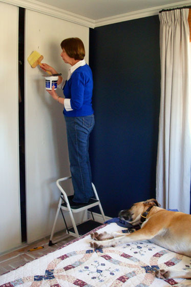 Brushing wallpaper paste onto the closet doors