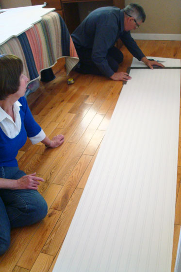 My parents measuring and cutting beadboard wallpaper