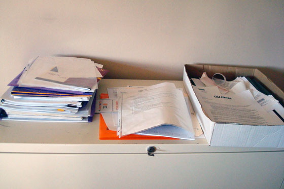 Piles of paper on top of the filing cabinet