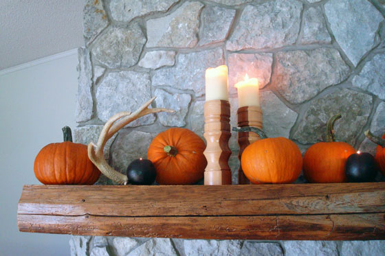 Pumpkins, antlers and candles decorating the mantel