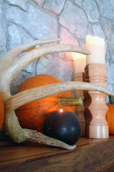 Antler, pumpkins and candles decorating a fall mantel