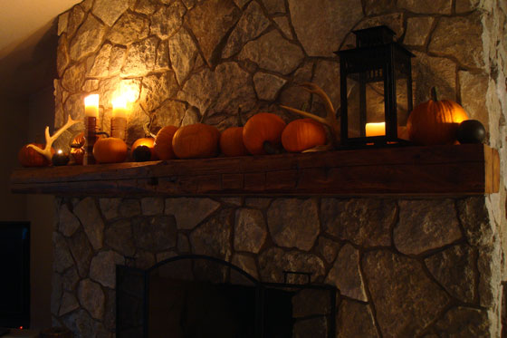 Candles lit on the fall mantel
