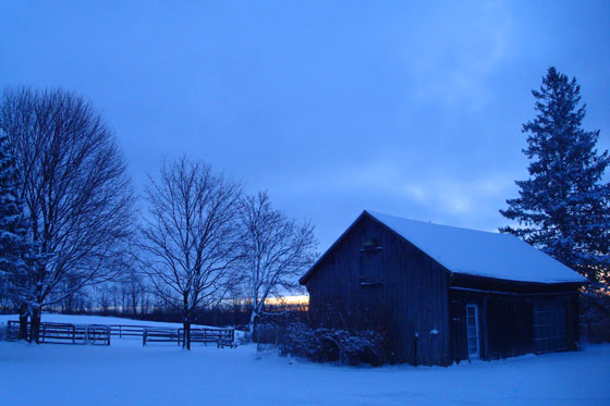 Sun rising over snow covered farm