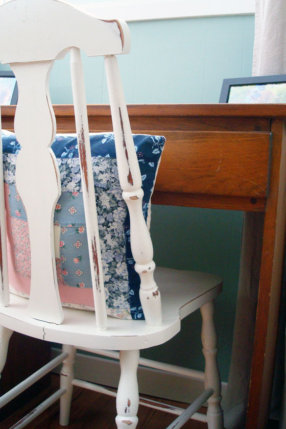 Distressed painted chair in front of a pine desk