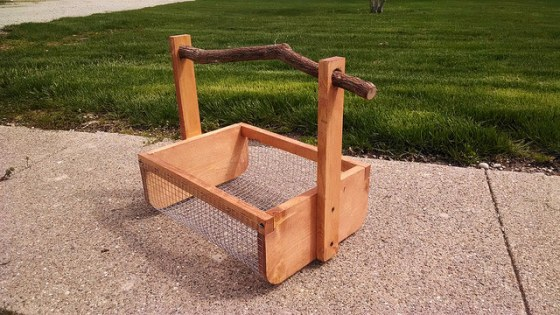 Wooden vegetable harvest basket with a twig handle