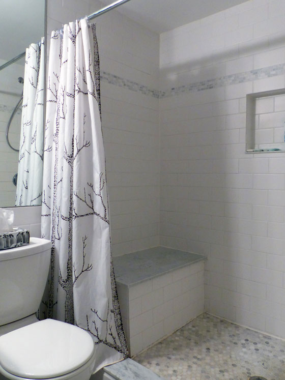 White subway tile shower with a marble seat
