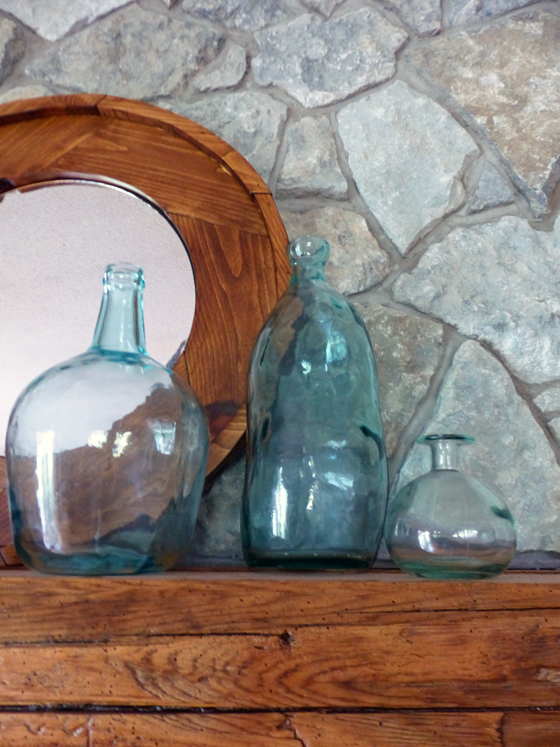 Blue-green glass jugs on the mantel