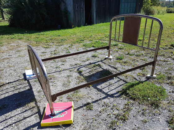 Metal bed frame set up on the driveway for painting