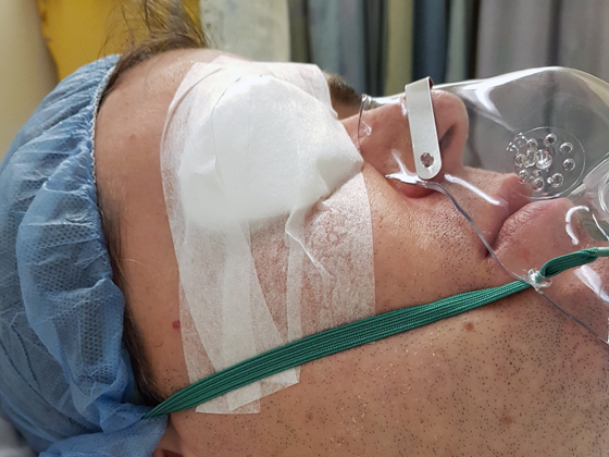 Wearing an eye patch and oxygen mask after surgery