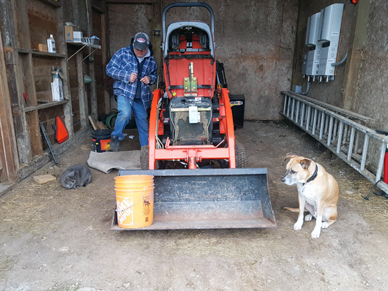 Ralph and Baxter supervising the oil change on the tractor