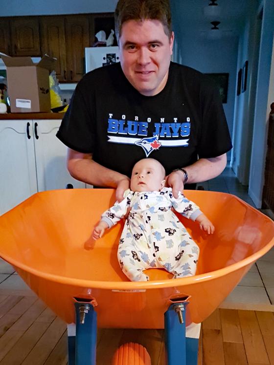 Matt holding Ellie in the wheelbarrow
