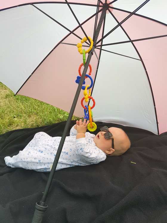 Baby wearing sunglasses lying outside under an umbrella