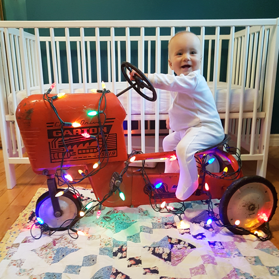 Ellie sitting on her tractor decorated with Christmas lights