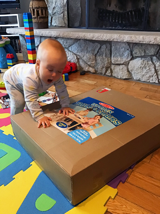 Baby leaning on a box