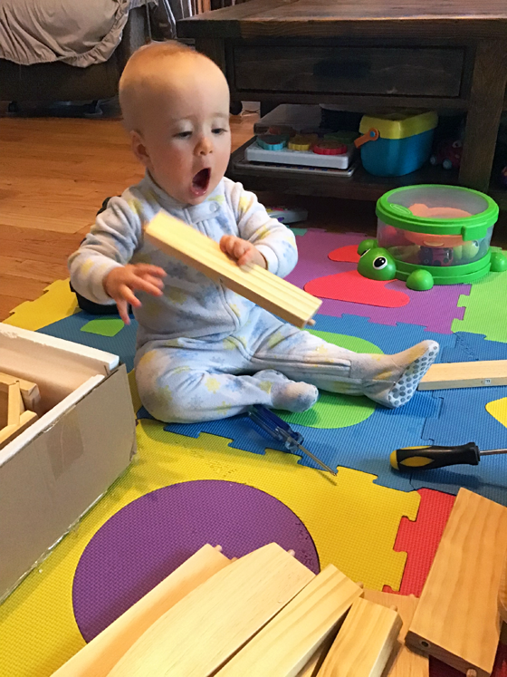 Baby excited to be holding a piece of wood
