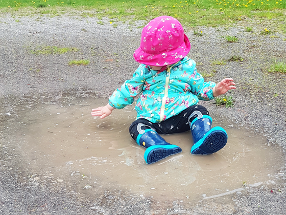 Baby sitting in a puddle on the driveway