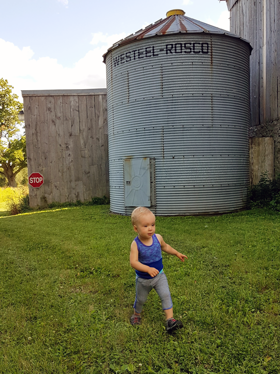 Ellie running past the metal grain silo