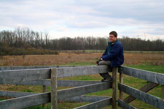 Matt sitting on a fence at the farm