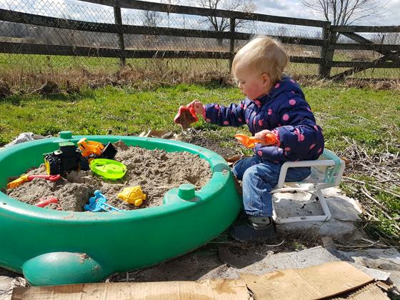Ellie playing in her sandbox in the garden
