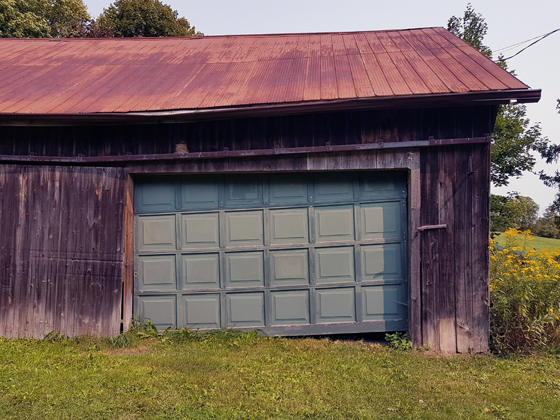 Broken garage door on the small barn