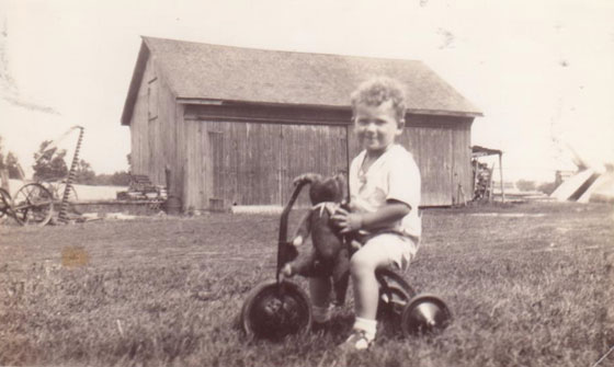 Black and white photo of a child riding a tricycle in front of a small barn