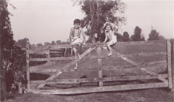 Black and white photo of two children sitting on top of a wood gate