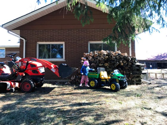 Two tractors (one a toy) in front of a pile of firewood