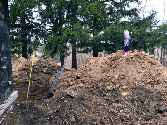 Child standing on top of a pile of dirt