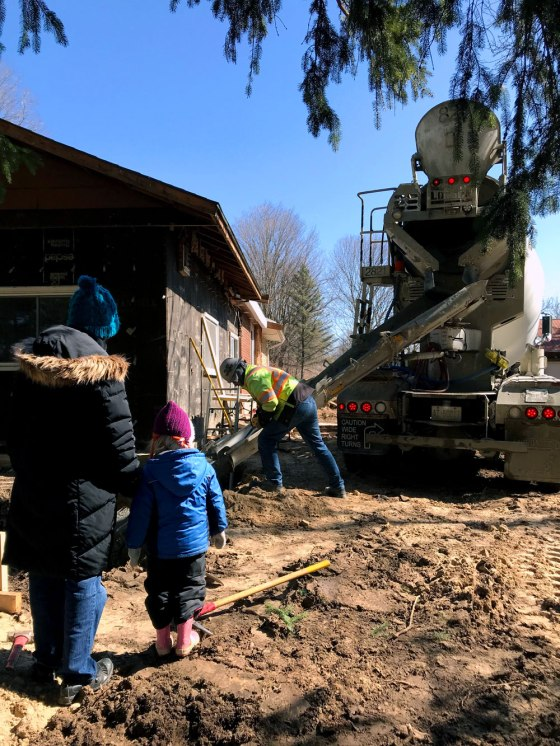 Child watching a cement truck pour cement